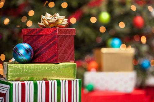 Фото Новогодние подарки и елочная игрушка на фоне елки