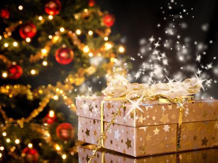 Фото Сверкающий новогодний подарок лежит на фоне елки