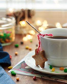 Фото Чашка кофе на блюдце с печеньем-звездочкой на ниточке и россыпью разноцветного драже на столе, by Natalya Rudikovskaya