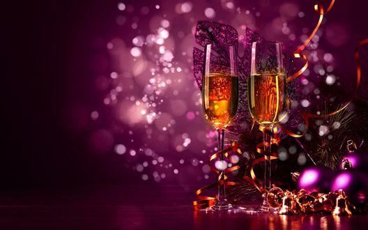 Фото Новогодняя композиция с бокалами, игрушками, шарами и веткой ели, на фоне боке с бликами
