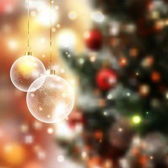 Фото Два прозрачных новогодних шарика со снежинками на размытом фоне наряженной елки