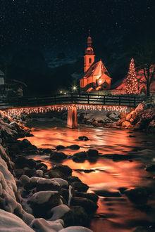 Фото Новогодняя елка у дома и светящаяся гирлянда на мосту над рекой