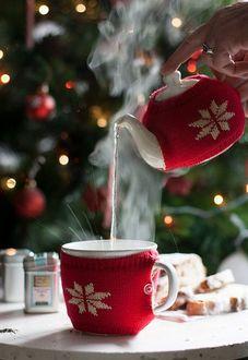 Фото В чашку наливают горячий чай, посуда украшена по новогоднему, на заднем плане новогодняя елка