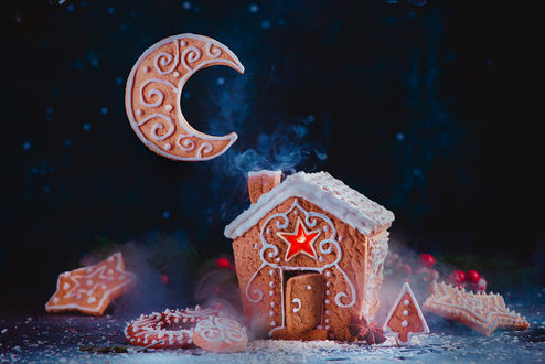 Фото Рождественская выпечка с пряничным домиком, сияющими карамельными окнами, бисквитом, с месяцем и восходящим дымом из дымовой трубы, фотограф Дина Беленко