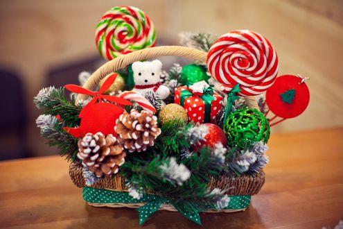 Фото Рождественская корзинка с елочными игрушками, леденцами и шишками