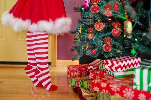 Фото Девочка в новогоднем наряде стоит на цыпочках и украшает елку, под которой лежат подарки