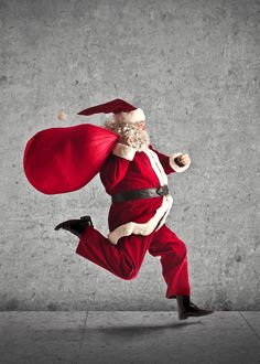 Фото Бегущий Санта-Клаус с мешком подарков на фоне бетонной стены