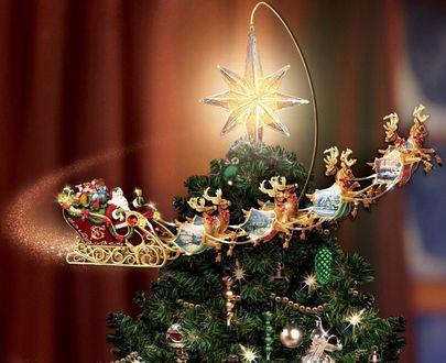 Фото Санта Клаус в санях, на оленях летит вокруг новогодней, наряженной елки