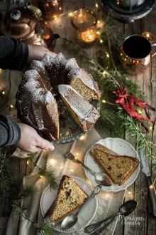 Фото Руки держат разрезанный новогодний пирог, на столе стоят тарелки с кусочками пирога, фигурка оленя и лежат еловые ветки, by Manzana&Canela