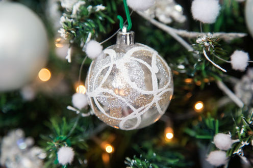 Фото Серебряный шарик висит на елке со светящейся гирляндой