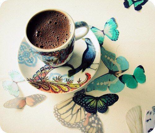 Фото Чашка с кофе на блюдце и бабочки на столе