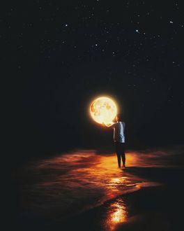 Фото Парень держит в руках луну, стоя в море (© chucha), добавлено: 13.01.2018 00:21