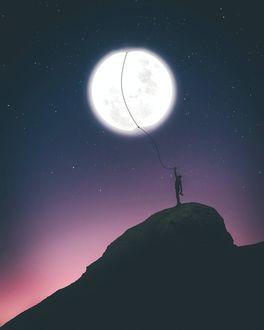 Фото Мужчина, стоящий на вершине горы, держит луну как воздушный шарик (© chucha), добавлено: 13.01.2018 00:36