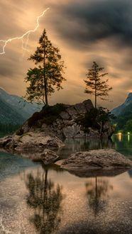 Фото Гроза на озере, молния освещает пасмурное небо, на небольшое скале посреди озера растут две сосны