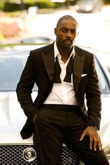 Фото Британский актер кино и телевидения Идрис Эльба / Idris Elba в черном смокинге сидит на капоте машины