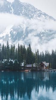 Фото Небольшой деревянный дом уютно расположился у подножия горы в лесу на берегу озера