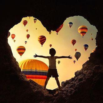 Фото Мальчик выглядывает из пещеры в форме сердца и смотрит на воздушные шары