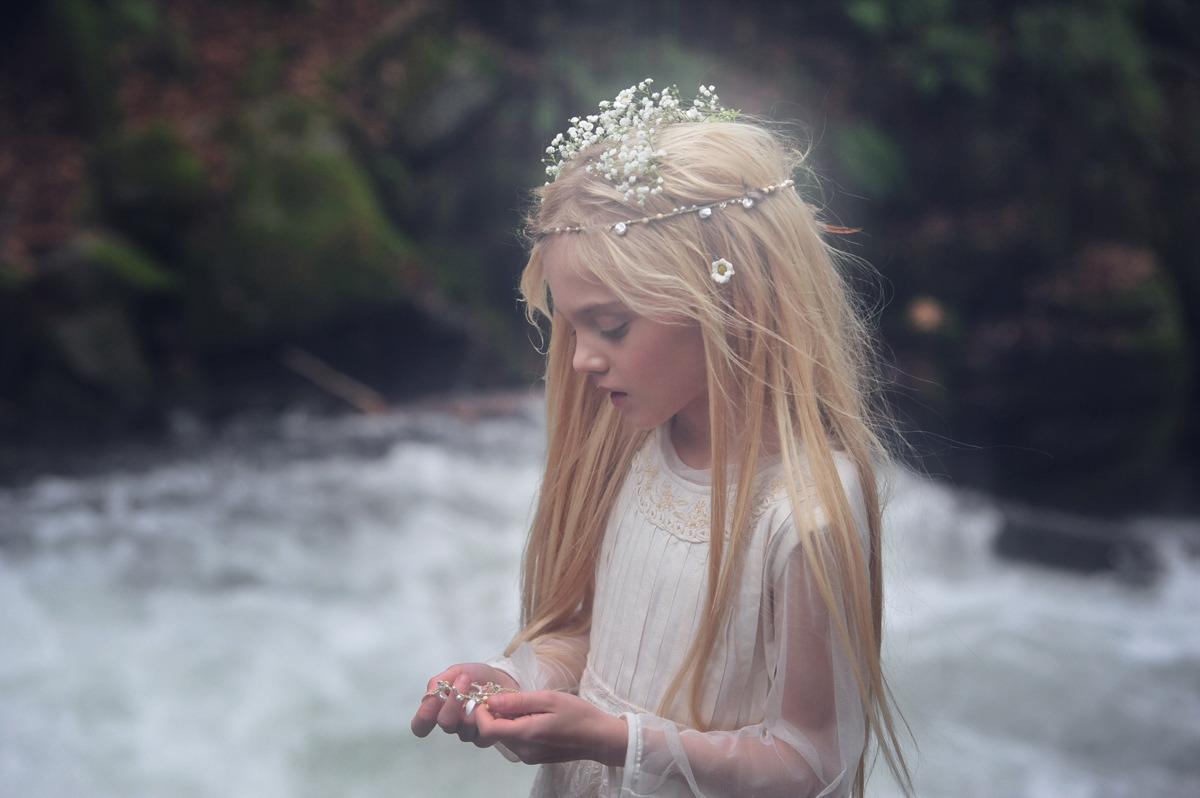 Фото Грустная девочка в венке cтоит на фоне реки, by KIN FABLES