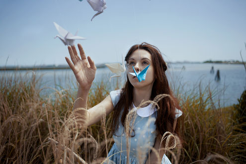 Фото Девушка с оригами в высокой траве перед рекой, by Elisa Paci