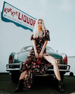 Фото Девушка-блондинка в цветном платье и полусапожках сидит на капоте авто