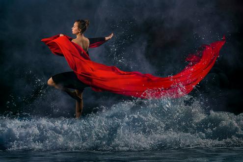 Фото Девушка с красной развевающейся тканью стоит в воде