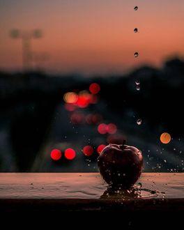 Фото Красное яблоко, на которое капает вода, лежит на фоне ночных огней авто