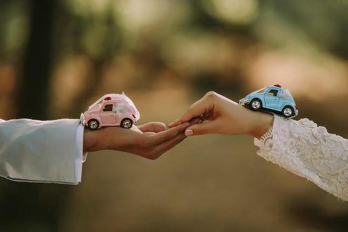 Фото Игрушечные машинки на руке парня и девушки