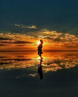 Фото Девушка стоит в воде на фоне заката