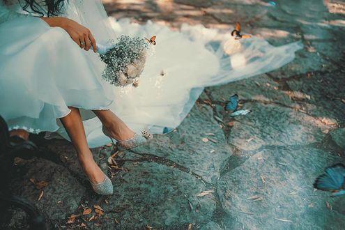 Фото Невеста с букетом цветов сидит на асфальте