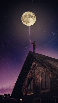 Фото Мальчик, стоя на крыше дома, держит на ниточке полный месяц