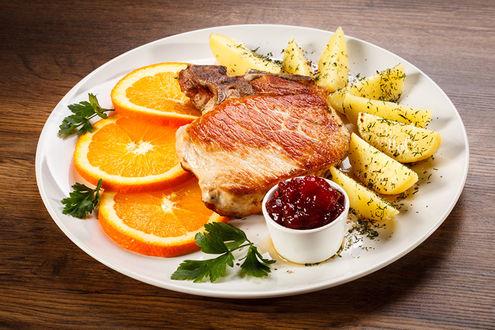 Фото Тарелка с отбивной, картошкой фри и апельсином