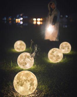 Фото Девушка с фонариком стоит в траве, перед ней лежат пять лун