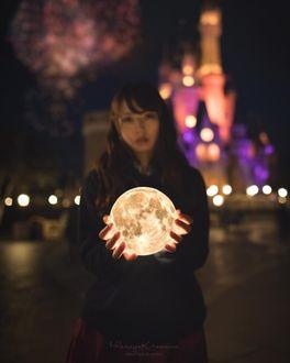 Фото Девушка держит в руках луну