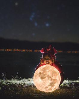 Фото Ребенок, перед которым лежит луна, сидит в траве