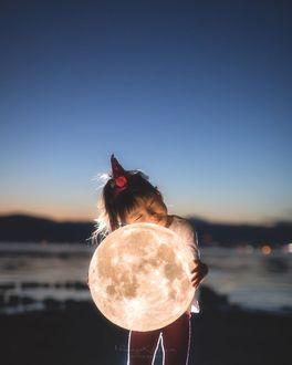 Фото Девочка обнимает луну, стоя на берегу моря