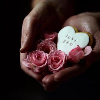 Фото В руке девушки розы и печенье в форме сердечка с надписью Love you / люблю тебя