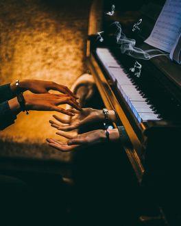 Фото Прикосновение рук девушки и мужчины, появившихся из под клавиатуры пианино
