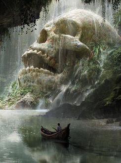 Фото Человек в лодке плывет по воде мимо скал, над одной из которых лежит огромный череп, по которому стекает вода