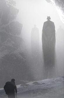 Фото Мужчина с рюкзаком за спиной в горах, перед ним стоят огромные рогатые монстры