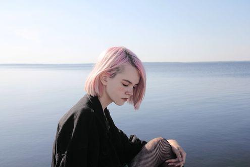 Фото Розоволосая девушка с веснушками, в черной одежде, сидит на фоне моря