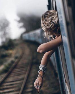 Фото Девушка выглядывает из окна поезда
