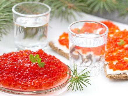 Фото Две стопки водки с пиалой красной икры и бутербродами