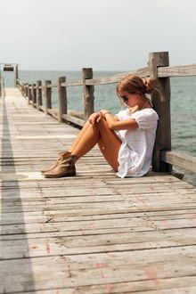 Фото Девушка в белом платье, в очках сидит на мосту