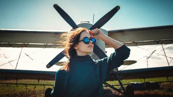 Фото Девушка в очках стоит перед самолетом