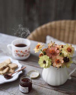 Фото Чашка горячего кофе, печенье на тарелке и цветы в кувшинчике стоят на столе