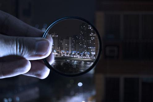 Фото Сквозь увеличительное стекло видна панорама ночного города