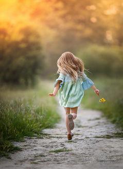 Фото Девочка с цветочком в руке бежит по тропинке, фотограф Lilia Alvarado
