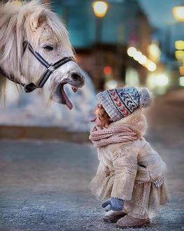 Фото Девочка и лошадь показывают друг другу язык
