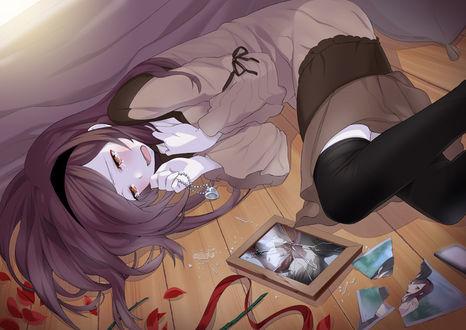 Фото Плачущая девушка с кулоном в руке лежит на полу возле разбитой рамки с фотографией
