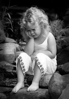 Фото Милая грустная девочка сидит на камнях